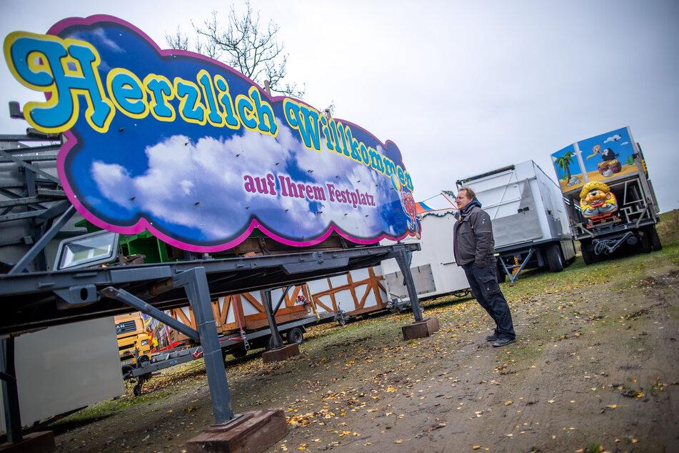 """Marco Welte steht auf dem Firmengelände der Schausteller-Familie Welte vor dem Eingangstor für einen Festplatz mit der Aufschrift """"Herzlich Willkommen""""."""
