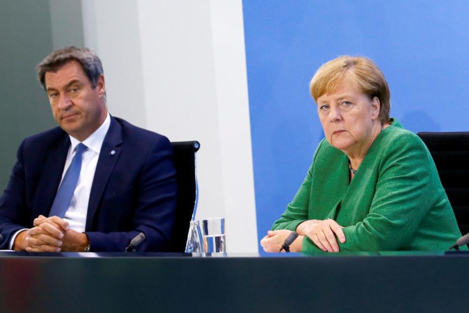 Bundeskanzlerin Angela Merkel (CDU) sitzt mit dem bayerischen Ministerpräsidenten Markus Söder (CSU) bei einer Pressekonferenz im Kanzleramt.