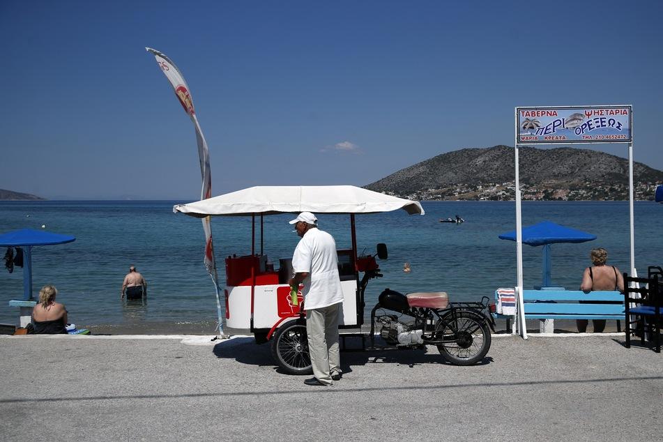 Ein Eisverkäufer wartet am Strand von Griechenland auf Kundschaft.