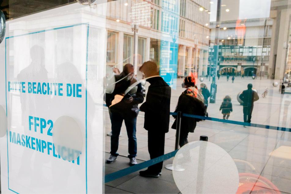 Ein Hinweisschild zum Beachten der FFP2-Maskenpflicht hängt am Eingang eines Bekleidungsgeschäftes am Alexanderplatz.