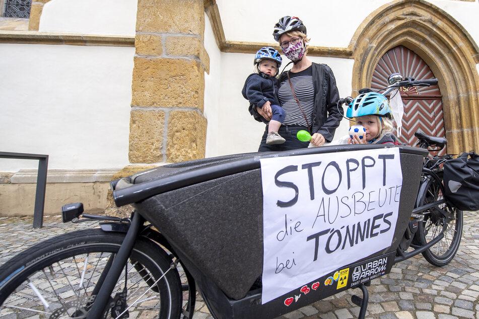 Nicole Ritschel ist mit ihren Töchtern Paula (l.) und Frieda auf einem Fahrrad zur Mahnwache zur Situation beim Fleischwerk Tönnies auf dem Marktplatz in Rheda-Wiedenbrück gekommen.