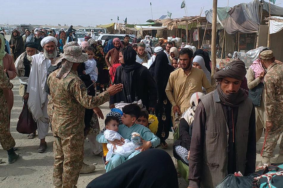 Pakistanische Soldaten überprüfen die Papiere von Menschen, die die Grenze zu Afghanistan an einem Grenzübergang überqueren.