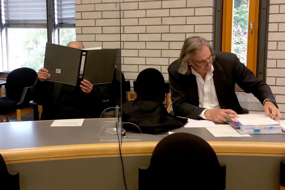 Baden-Baden, Ende September: Der Angeklagte hält sich vor Prozessbeginn im Gerichtsaal einen Aktenordner vor sein Gesicht. Rechts sitzt sein Anwalt Andreas Kniep.