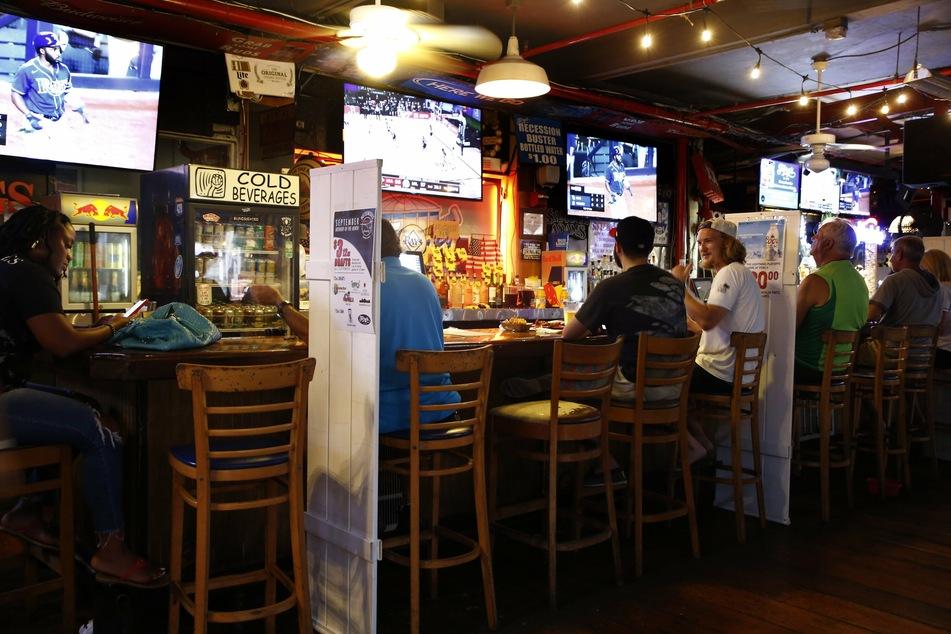 USA, St. Petersburg: Baseballfans in der Ferg's Sports Bar verfolgen das Spiel der Tampa Bay Rays gegen die New York Yankees. Wegen der Corona-Pandemie gibt es in vielen Bars Vorrichtungen, um den Mindestabstand zu gewähren.