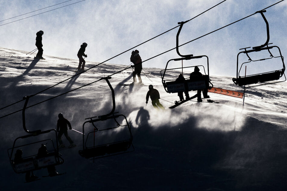 Skifahrer fahren bei starkem Wind eine Piste in Leysin (Schweiz) herunter.