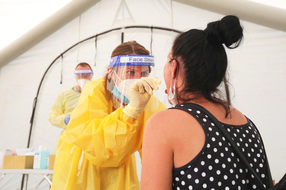 Eine Mitarbeiterin der Malteser nimmt einen Abstrich bei einer Reiserückkehrerin.