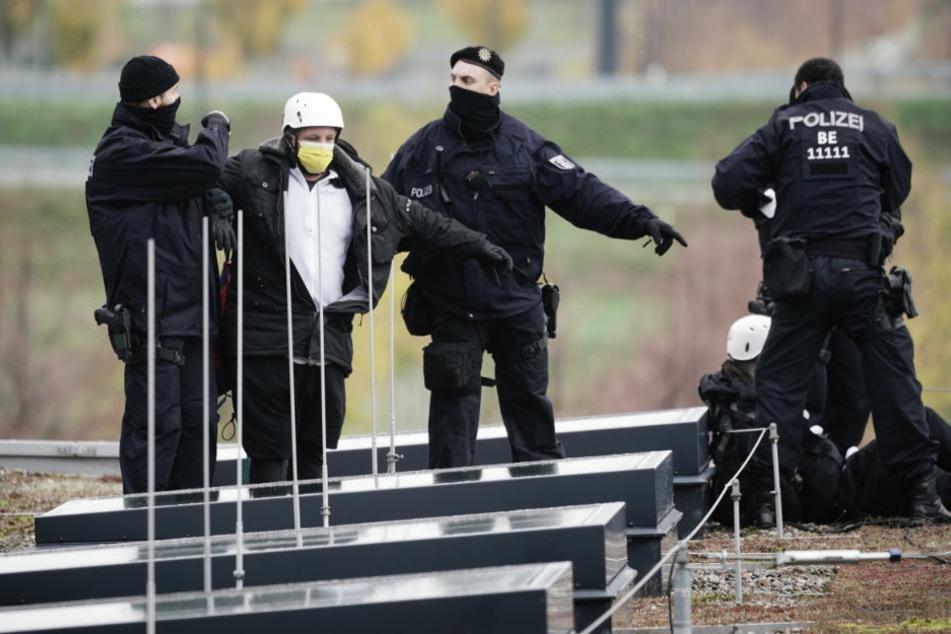 Polizisten begleiten Demonstranten vom Dach vor Terminal 1 am neuen Hauptstadtflughafen BER. Mehrere Gruppen hatten angekündigt, die Eröffnung massiv stören zu wollen.