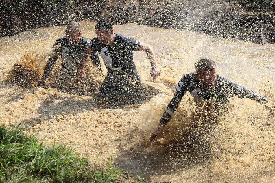 """Beim nicht alltäglichen Geländelauf """"Mudder Island"""" auf der Ostseeinsel Poel müssen Teilnehmer ein Wasserloch durchqueren."""