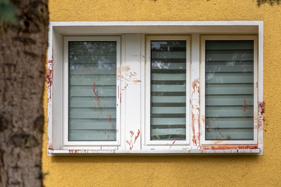 Das Fenster vor einer Wohnung des Mehrfamilienhauses in vollgeschmiert mit Blut.