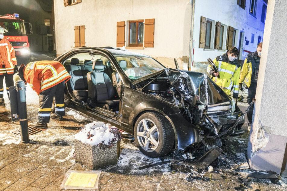 Einsatzkräfte begutachten an der Unfallstelle den völlig demolierten Wagen. Eine 24-Jährige war betrunken in den Hauspfeiler gekracht.