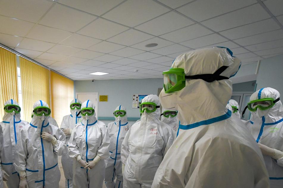 Mediziner mit Schutzanzügen stehen während einer morgendlichen Besprechung im Krankenhaus des Nationalen Medizinischen und Chirurgischen Zentrums Pirogov.