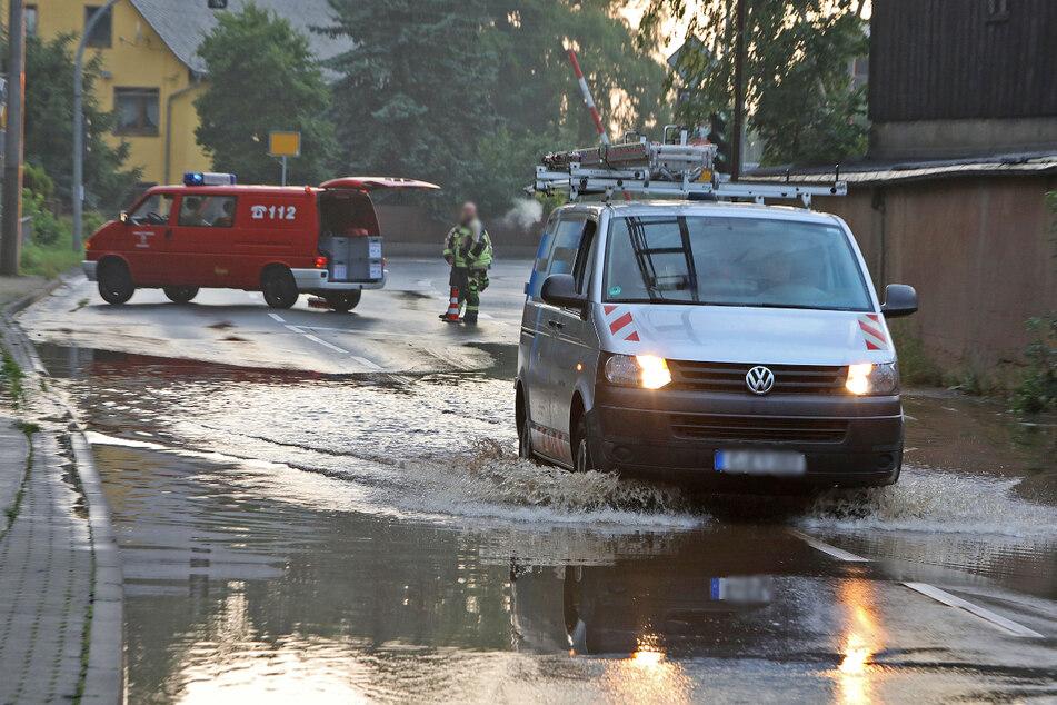 Land unter auf der B180 in Oberlungwitz: Ein Transporter bahnt sich seinen Weg auf der überfluteten Straße.