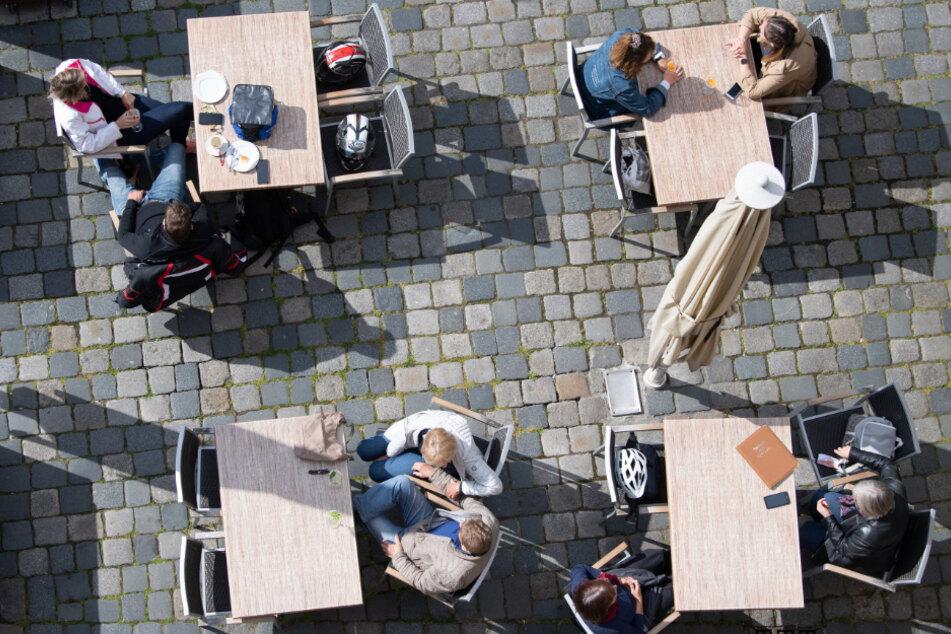 Gäste sitzen auf dem Neumarkt in einem Cafe.