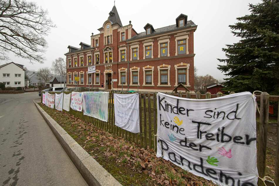 Eltern haben vor einer Kita in Plauen Plakate aufgehängt. Sie fordern sofortige Öffnungen.