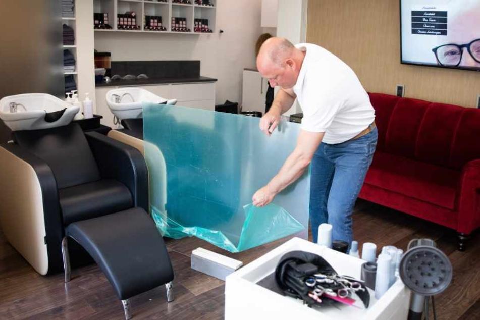 Birger Kentzler, Verbandsvorsitzender der Friseur-Innung Hamburg, montiert einen Plexiglasschutz zwischen den Haarwaschbecken in seinem Salon.