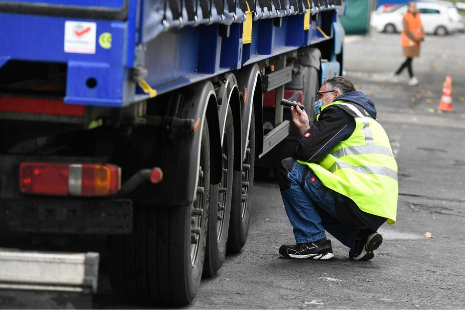 Ein TÜV-Mitarbeiter überprüft die Bremsen eines Lastwagens. (Symbolbild)
