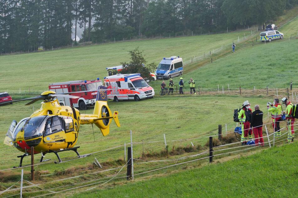 Einsatzkräfte stehen an einem Waldstück, in das ein kleines Flugzeug gestürzt ist.