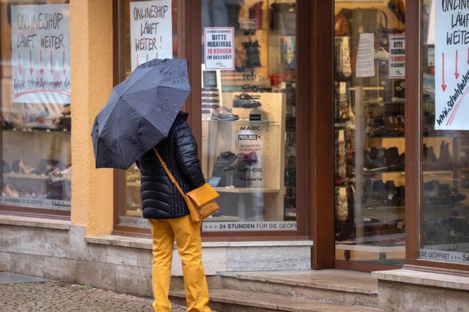 Eine Frau steht vor einem geschlossenen Schuhgeschäft in Gotha. Thüringen kämpft weiterhin mit zu hohen Neuinfektionen.