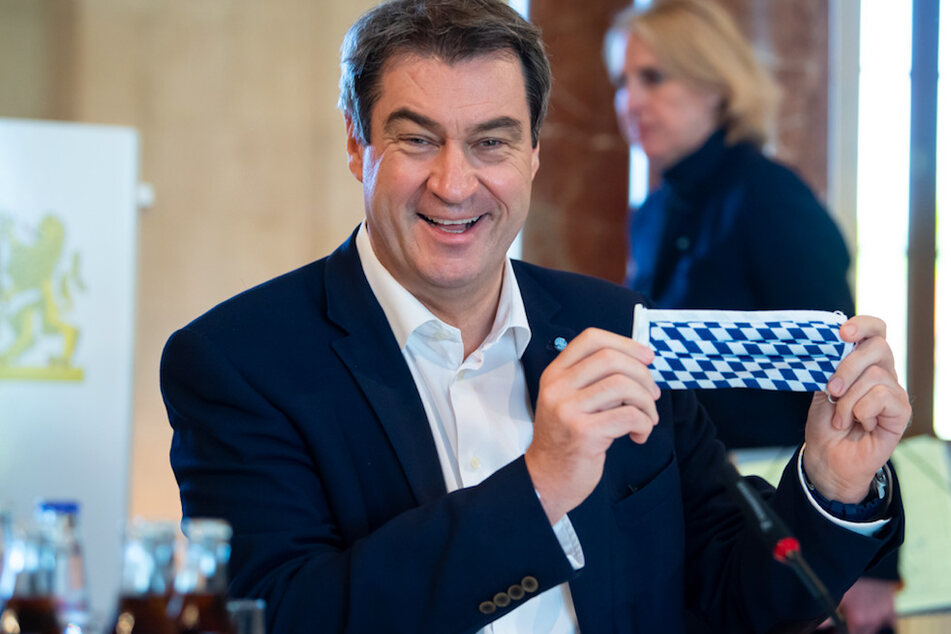 Markus Söder (CSU), Ministerpräsident von Bayern, nimmt an einer Sitzung des bayerischen Kabinetts teil und hält dabei einen Mundschutz mit der bayerische Rautenflagge in den Händen.
