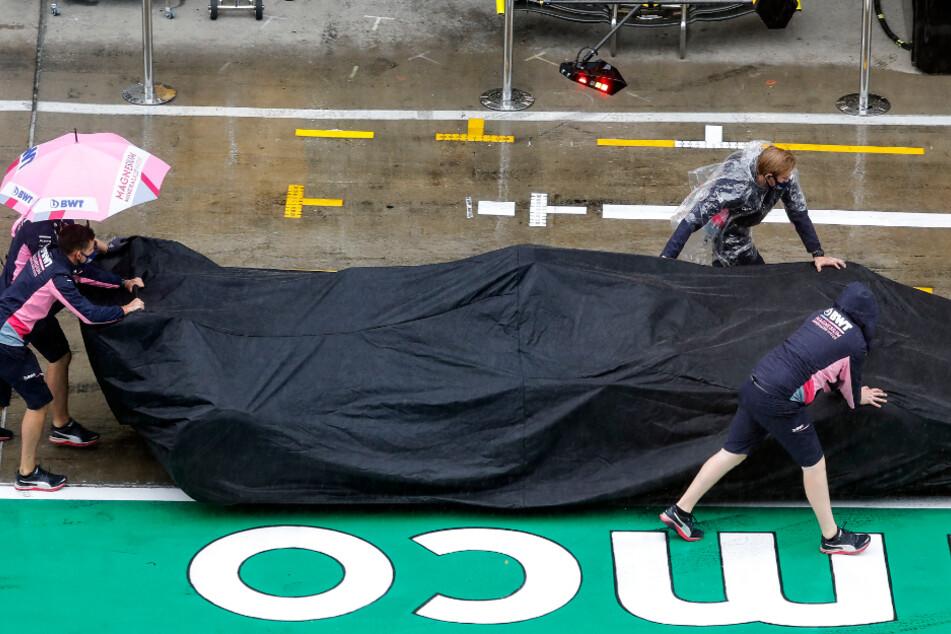Der Rennwagen von Perez vom Team Racing Point wird unter einer Abdeckung über die Boxengasse geschoben.