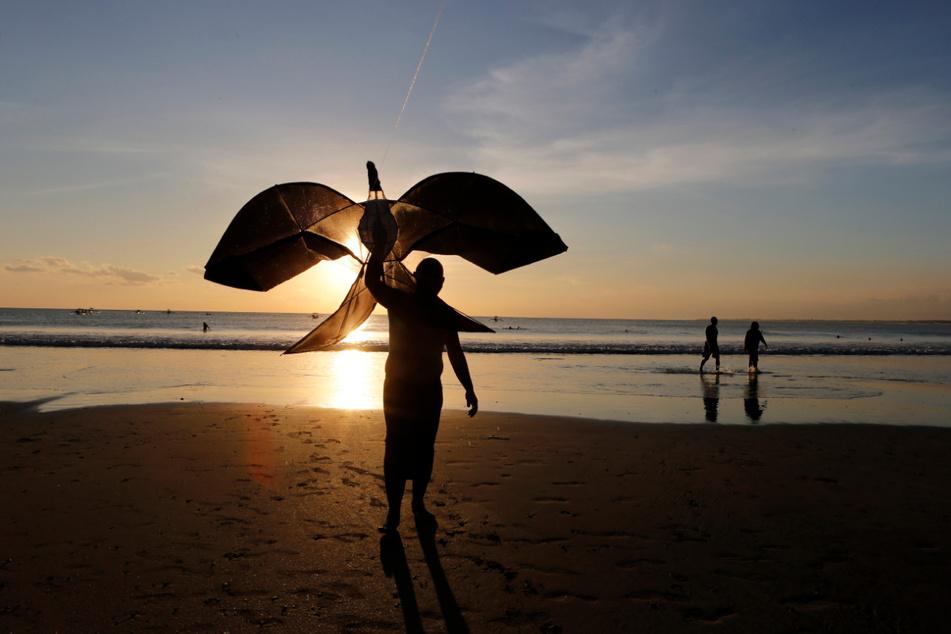 Ein Mann steht mit einem Drachen bei Sonnenuntergang an einem Strand auf Bali.