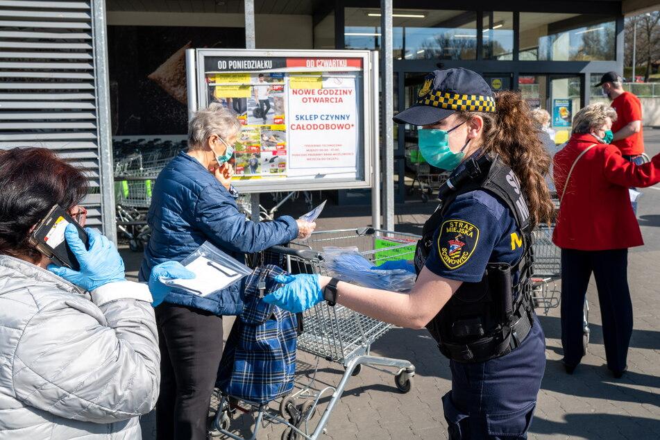 Ein Mitglied der Stadtpolizei verteilt Schutzmasken an Seniorinnen vor einem Supermarkt in Sosnowiec. In der ganzen Stadt werden von Mitgliedern der freiwilligen Feuerwehr, der Stadtwache und Freiwilligen zehntausende Schutzmasken verteilt.