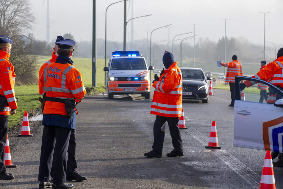 Belgien, Brüssel: Polizisten halten während einer Kontrolle am Parkplatz Aire de Hondelange an der Autobahn E411 ein Fahrzeug an.