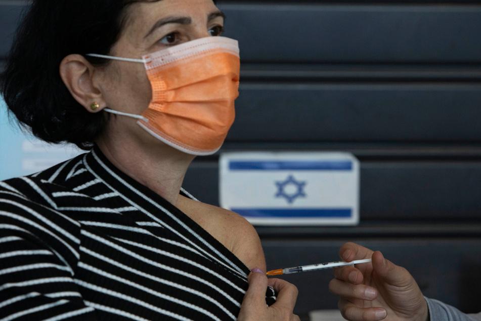 Israel, Tel Aviv: Eine israelische Frau erhält in einem Impfzentrum einen Pfizer-BioNTech-Corona-Impfstoff.
