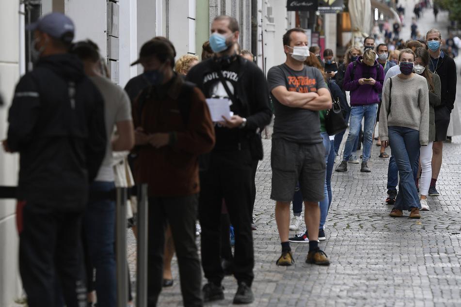 Menschen mit Mundschutz stehen an der Sammelstelle am Wenzelsplatz Schlange, um sich auf Covid-19 testen zu lassen.