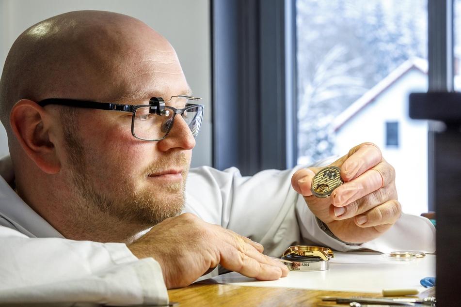 Uhrmachermeister Lars Timmler (34) schalt ein Uhrwerk ins Gehäuse ein.