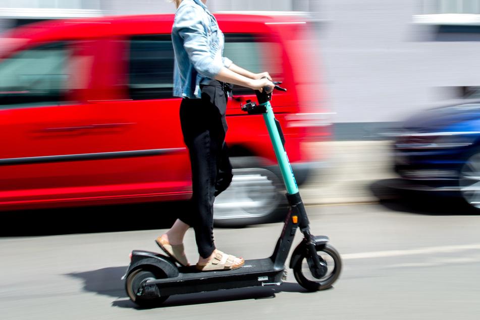 Eine junge Frau fährt mit einem E-Scooter des Anbieters Tier Mobility.