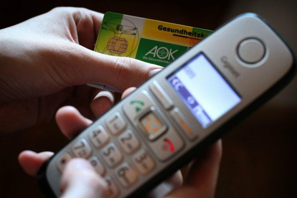 Gesundheitskarte in der Hand, zum Telefon gegriffen und beim Arzt angerufen: Das genügt meist weiterhin zur Krankschreibung. (Symbolbild).
