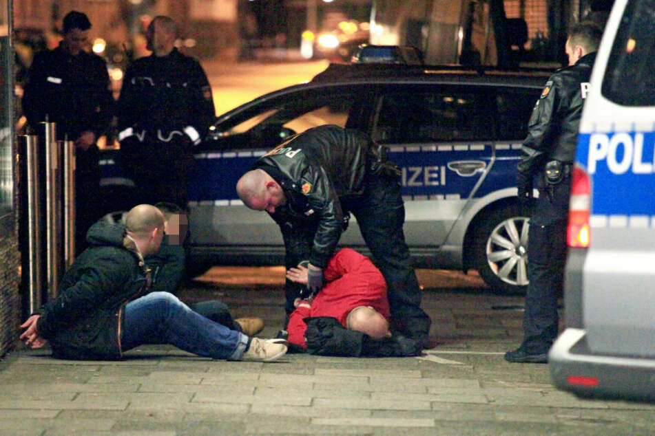 Ein Polizist fesselt in Bremen einen auf dem Boden liegendes Mitglied der Rockergruppen «Hell's Angels» in der bremer innenstadt