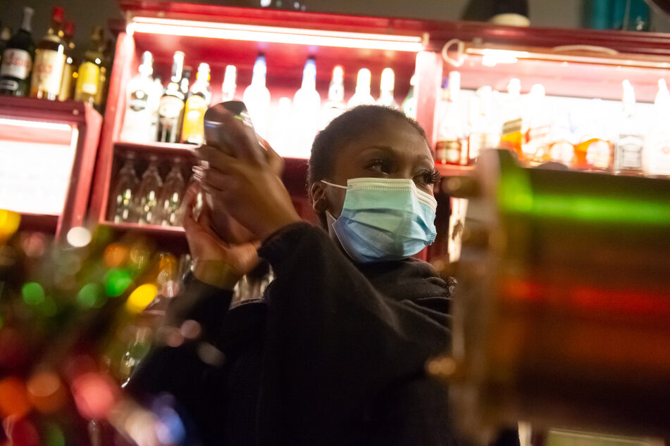 Eine Barkeeperin steht mit Mund-Nasen-Schutz hinter dem Tresen einer Bar im Schanzenviertel.