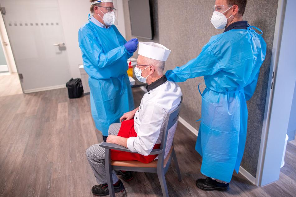 Schwerin: Der Koch Bernhard Bachert wird vom Arzt (l) als Mitarbeiter des Seniorenquartiers gegen Corona geimpft.