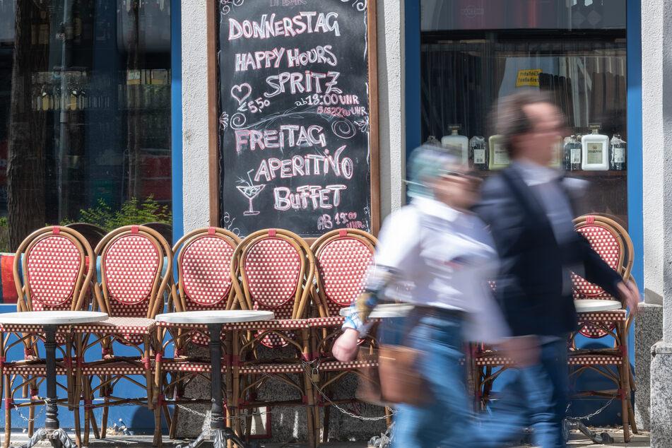 Passanten gehen an zusammengestellten Tischen und Stühlen eines geschlossenen Cafes vorbei. (Archivbild)