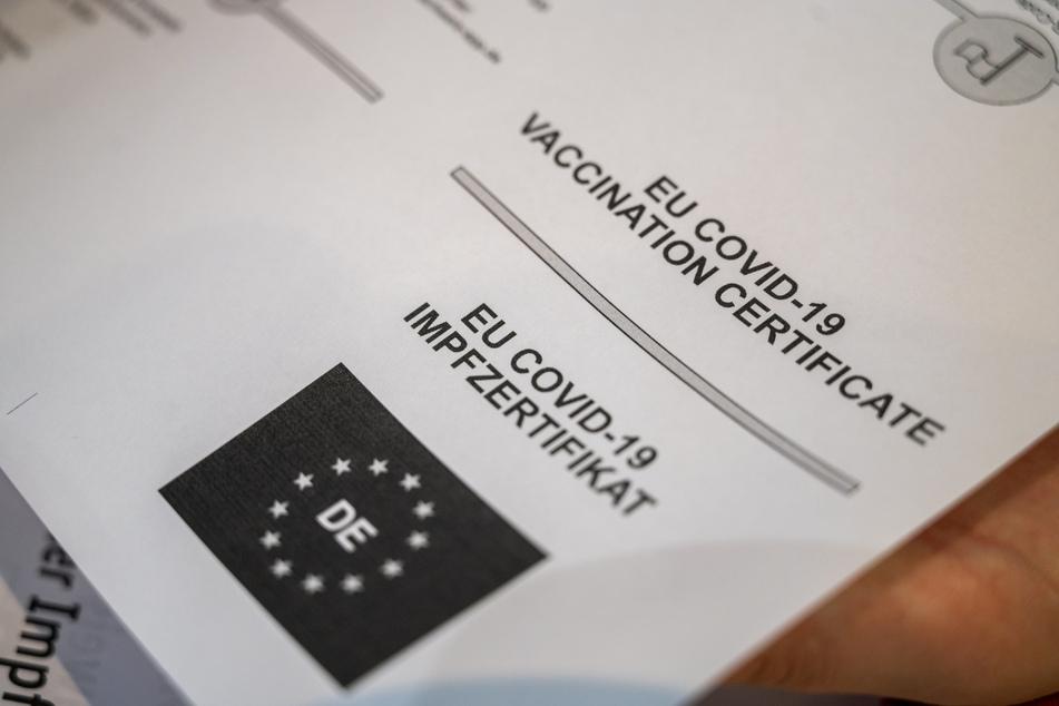"""Auf einem Dokument, das zum Digitalen Impfnachweis gehört steht """"EU Covid-19 Impfzertifikat"""" auf englisch und auf deutsch."""