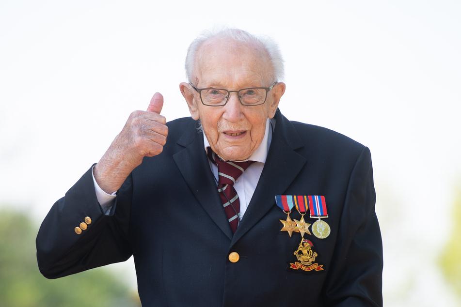 Der Kriegsveteran Tom Moore zeigt seinen Daumen nach oben. Der inzwischen 100 Jahre alte Brite, der mit seinem Spendenlauf am Rollator einen Weltrekord aufgestellt hat, wird zum Ritter geschlagen.
