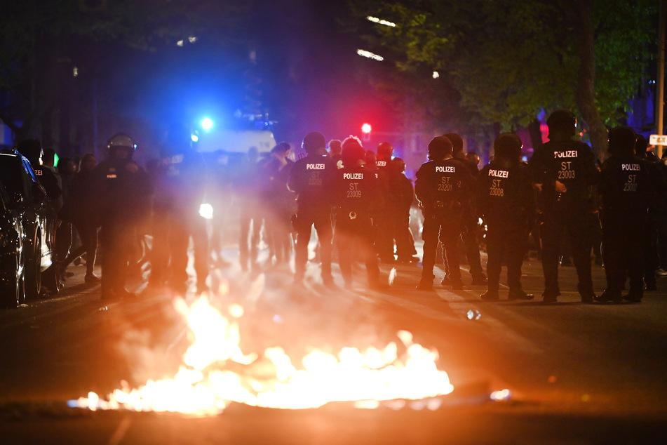 """Polizei am Rande der Demonstration linker und linksradikaler Gruppen unter dem Motto """"Demonstration zum revolutionären 1. Mai"""", im Vordergrund ein Feuer auf der Straße."""