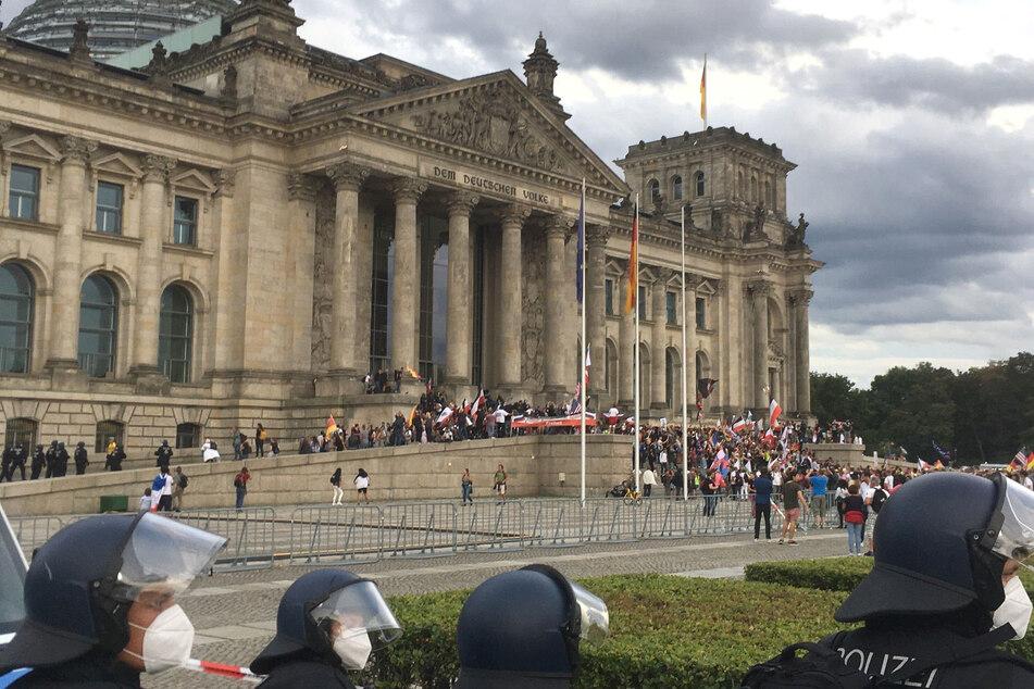 Teilnehmer der Kundgebung gegen die Corona-Maßnahmen stehen vor dem Reichstag in Berlin.