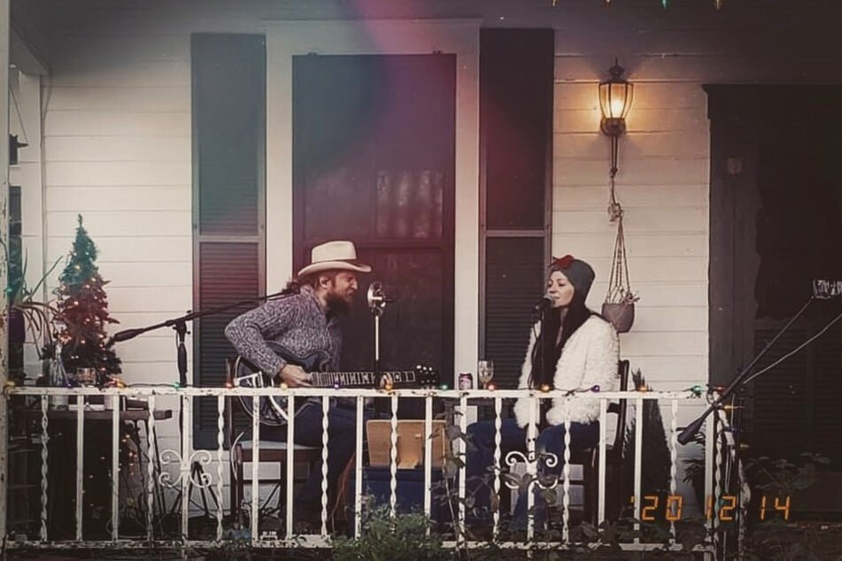 Nick and Paige DeChausse perform as The Reverent Few on their front porch.