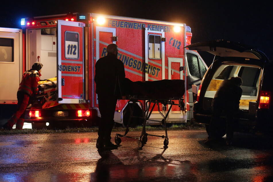 Bestatter verladen das Unfallopfer in einen Leichenwagen.