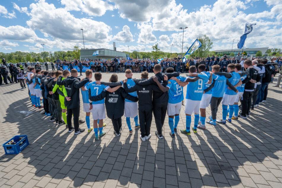 Die Mannschaft von 1860 München steht nach der bitteren Niederlage vor ihren mitgereisten Fans.