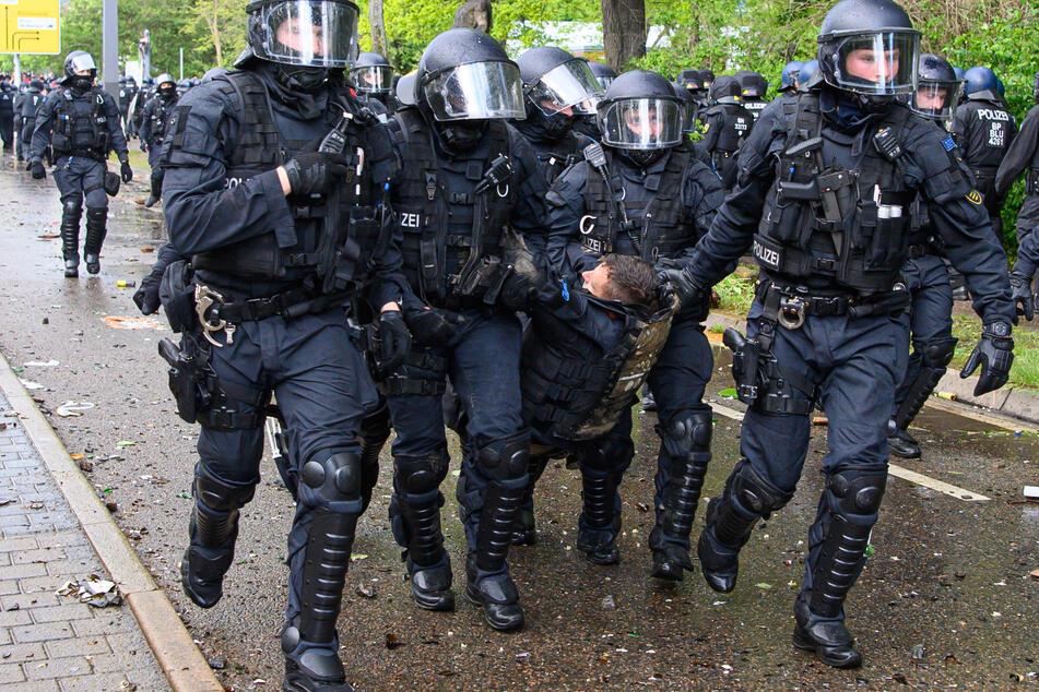 Polizisten tragen einen Kollegen weg. Bei Ausschreitungen gab es über 200 Verletzte.