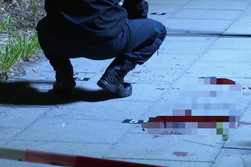 Ein Polizist kniet neben einer Blutlache. Ein 45-jähriger Mann ist bei einem Messerangriff auf St. Pauli lebensgefährlich verletzt worden.