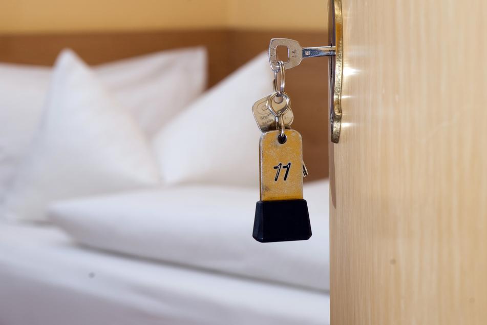 Ein Zimmerschlüssel hängt in einem Gästehaus vor einem Bett im Türschloss.