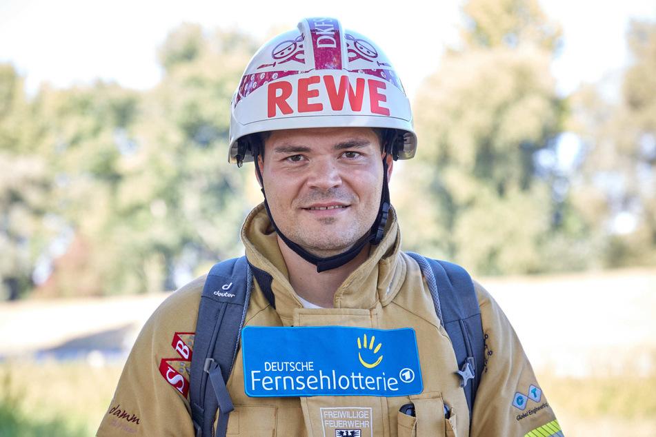 Mario Schnepf, Berufsfeuerwehrmann, steht in feuerfester Kleidung, inklusive Schutzhelm am Straßenrand.