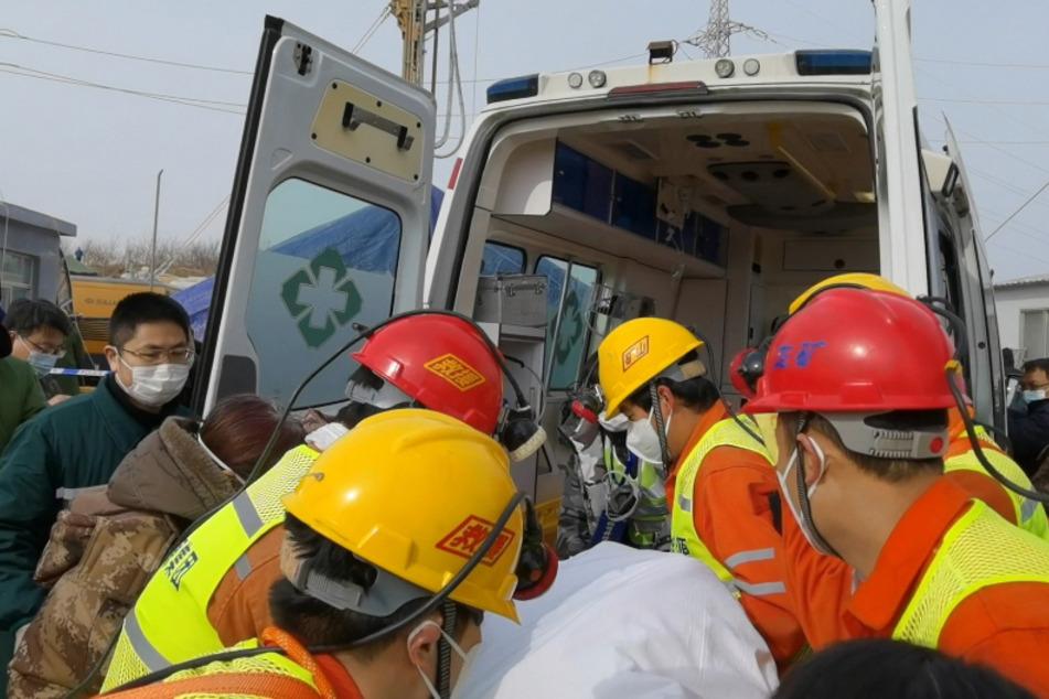 Retter tragen einen eingeschlossenen Bergarbeiter zu einem Krankenwagen.