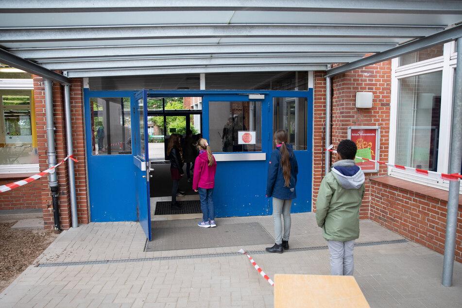 Schüler einer 4. Klasse stehen nach den geltenden Abstandsregeln vor ihrer Schule.
