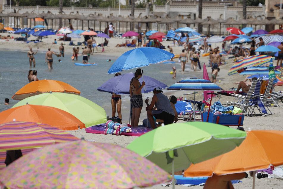 Urlauber suchen auf der Insel Mallorca am Strand Schatten unter Sonnenschirmen.